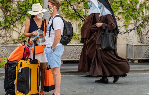 Dos turistas esperan en la calle mientras pasan dos monjas; todos ellos, con mascarilla.