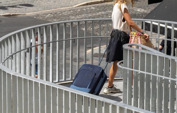 Una joven turista acarrea una maleta durante las vacaciones de 2020.