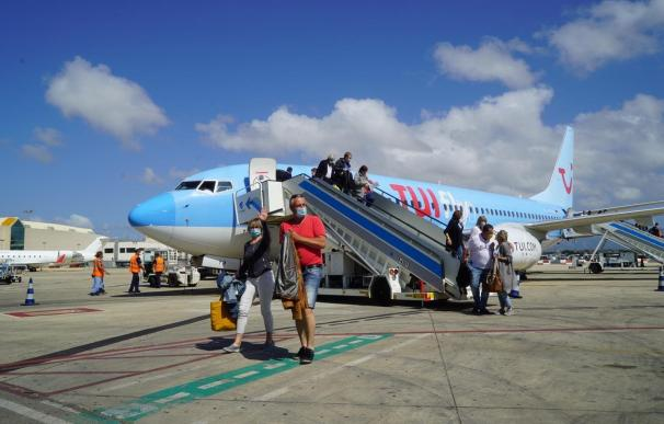 Varios turistas descienden en España de un avión operado por TUI.