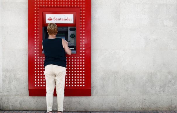 Una mujer saca dinero de un cajero del Banco Santander.