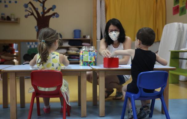 Una profesora atiende a dos niños en el regreso antes de las vacaciones del verano de algunas actividades de Infantill.