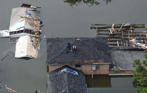 Dos vecinos esperan ser rescatados de un tejado en los días siguientes al paso del 'Katrina' por Nueva Orleans.