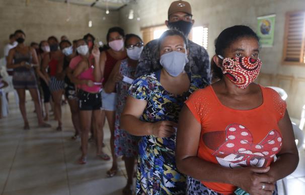 Un grupo de personas residentes de uno de los suburbios de Brasil esperan para recibir alimentos y material sanitario, en medio de la criris del coronavirus