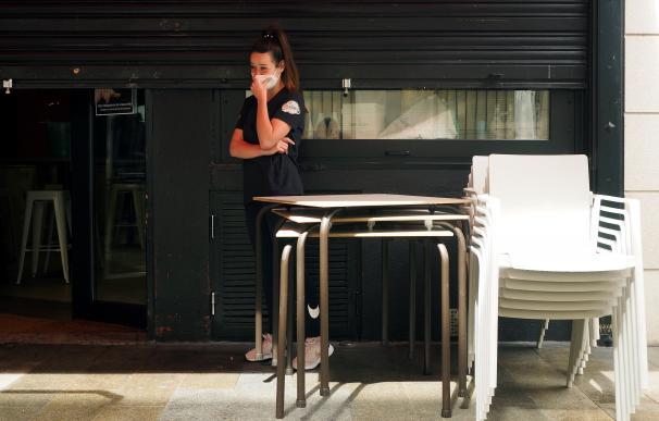 Una trabajadora en un bar de Lugo contempla el cierre de su establecimiento tras las nuevas medidas.