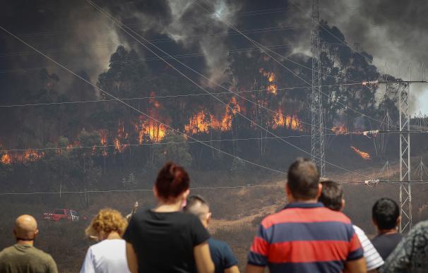 Vecinos de la localidad de Valverde del Camino observan la labores de extinción del incendio que afecta a la provincia de Huelva.