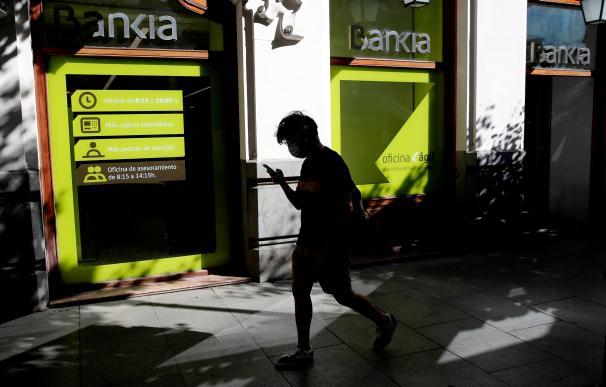 Un transeúnte pasa por delante de una oficina de Bankia.