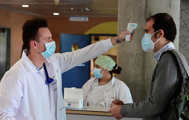 Un sanitario toma la temperatura a un hombre que accede al Hospital de Alcorcón en Madrid.