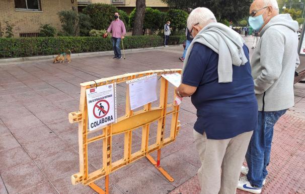 Un hombre toca un cartel para leer las medidas adoptadas frente al coronavirus este lunes en Alcobendas.