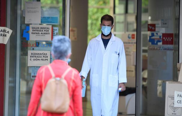 Un sanitario recibe a una paciente termómetro en mano en el centro de salud Federica Montseny en el distrito de Puente de Vallecas