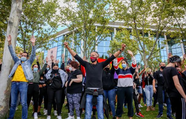 Varias personas levantan las manos durante una concentración bajo el nombre 'Más Sanidad, Menos Policía' frente a la Asamblea de Madrid en el barrio madrileño de Vallecas