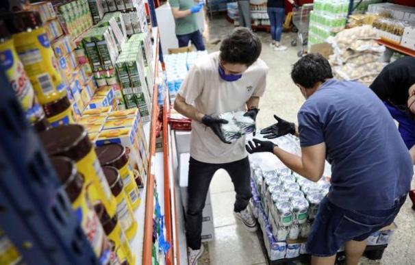 Trabajadores reponiendo productos en un supermercado