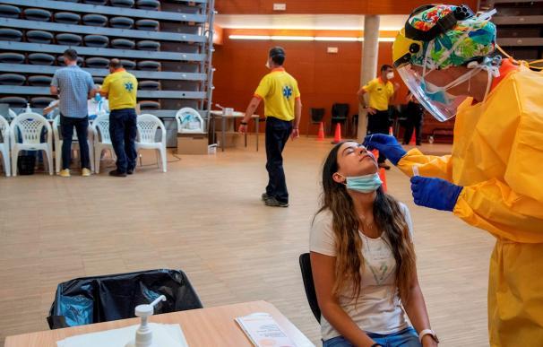 Una joven es atendida por un profesional sanitario para hacer una PCR.
