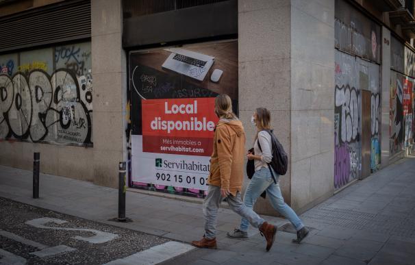 Dos personas caminan por una calle del Barrio Gótico ante un local cerrado en Barcelona.