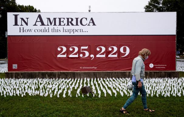Un hombre camina frente a un cartel con la cifra de muertos por Covid-19 en EEUU, en Washington