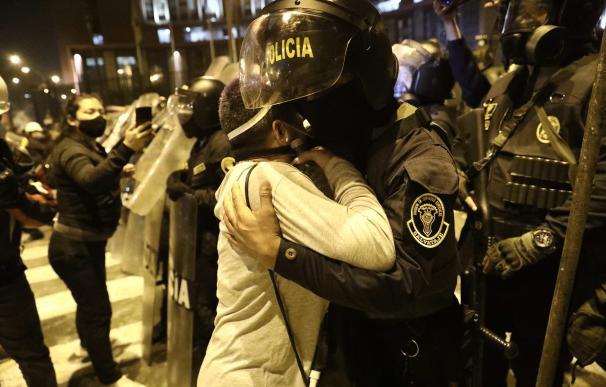 Una manifestante se abraza a una policía durante las protestas en Lima contra el Gobierno.