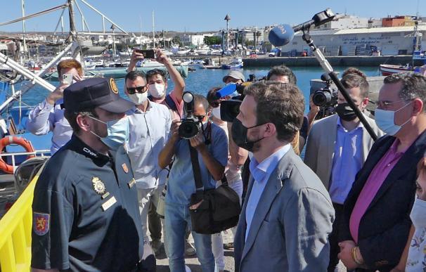 El líder del PP, Pablo Casado (d), conversa con un agente durante su visita al Muelle de Arguineguín (Gran Canaria) tras anularse la convocatoria inicial prevista en la isla de El Hierro, en Gran Canaria, Canarias, (España)