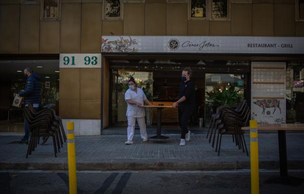 Dos mujeres sacan una mesa a una terraza durante el primer día del inicio del primer tramo de la desescalada de la segunda ola por el coronavirus en Barcelona, Catalunya (España), a 23 de noviembre de 2020. Desde hoy, bares y restaurantes podrán abrir de 6.00 a 21.30 para consumo en el establecimiento, el aforo en el interior estará limitado al 30%, y no podrá haber más de cuatro comensales por mesa --excepto si son del mismo grupo de convivencia--. 23 NOVIEMBRE 2020;CATALUÑA;BARCELONA;RESTAURACIÓN;HOSTELERÍA;BARES;RESTAURANTES;CAFETERÍAS;ECONOMÍA;NEGOCIO David Zorrakino / Europa Press 23/11/2020