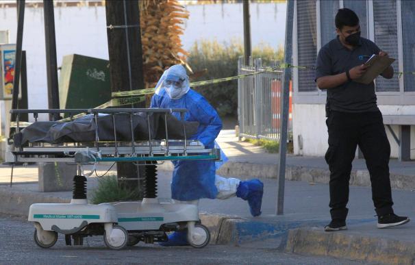 Un empleado de la Salud traslada al Servicio Médico Forense a una persona fallecida por la Covid-19 hoy, en el Hospital General de la fronteriza Ciudad Juárez, en el estado de Chihuahua (México).