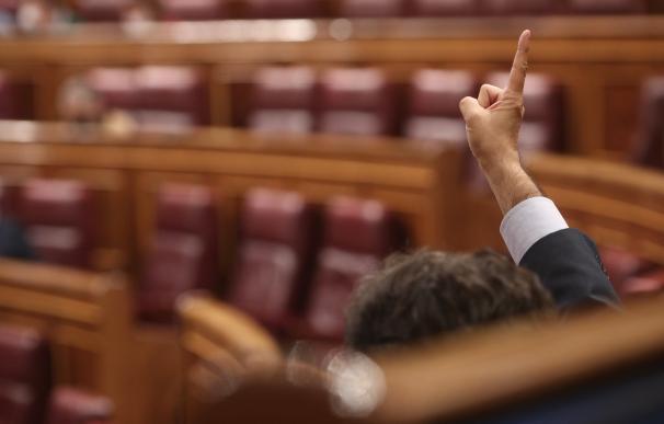 Un diputado del PP marca la votación durante una sesión del pleno del Congreso.