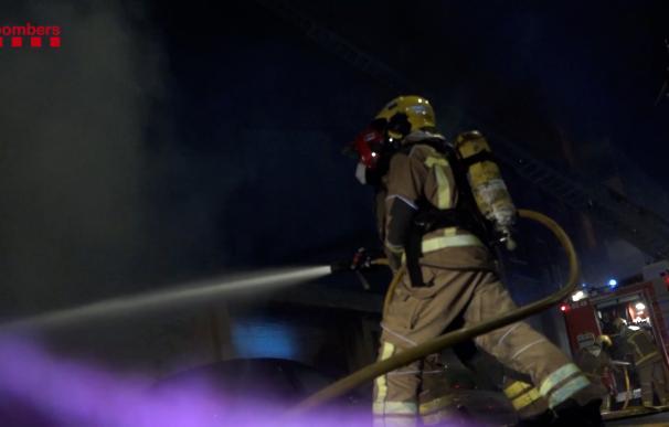 Los bomberos apagan el fuego en la nave okupada de Badalona