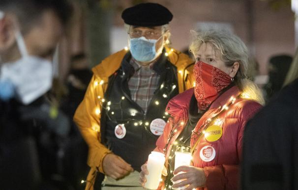 Dos personas con mascarilla en una manifestación contra las restricciones por la pandemia en Frankfurt