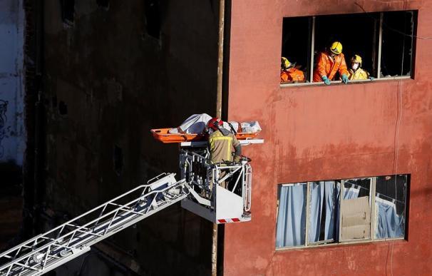 Los Bomberos sacan por la ventana de la nave uno de los cuerpos de las tres víctimas del incendio