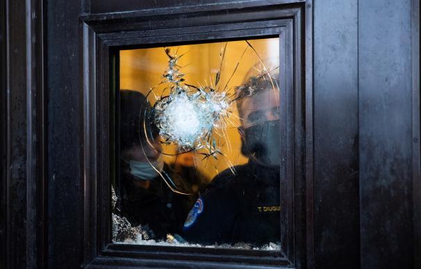 Dos policías observan a través del vidrio roto de una de las puertas del Capitolio de Estados Unidos.