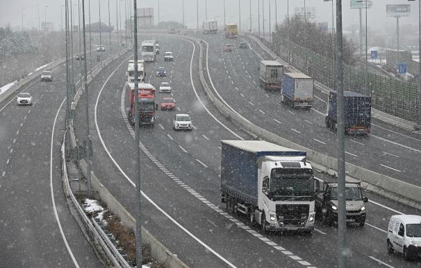 Varios vehículos circulan por la A-2 a su paso por la localidad madrileña de Alcalá de Henares bajo una intensa nevada.