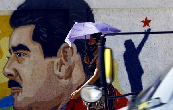 Una mujer camina bajo su paraguas frente a un mural con la imagen del presidente de Venezuela, Nicolás Maduro, en la ciudad de Guacara, en el norte del país. JUAN CARLOS HERNANDEZ / ZUMA PRESS / CONTACTOPHOTO (Foto de ARCHIVO) 23/11/2020 ONLY FOR USE IN SPAIN