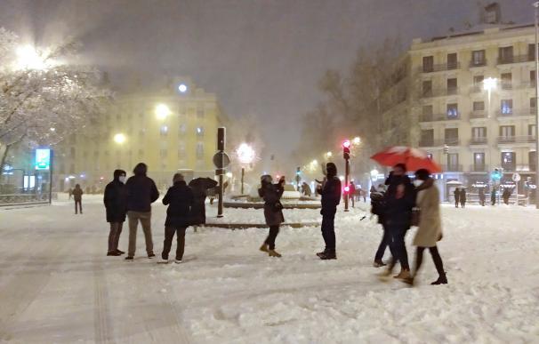 Varias personas disfrutan de la nieve esta noche en la glorieta de Bilbao de Madrid. La península sigue afectada por el temporal Filomena que deja grandes nevadas y temperaturas más bajas de lo habitual.