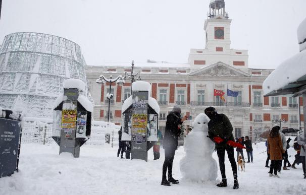 Una pareja hace un muñeco de nieve en la Puerta del Sol en Madrid