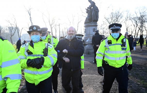 Varios policías custodian a un manifestante contra las restricciones en el Reino Unido.