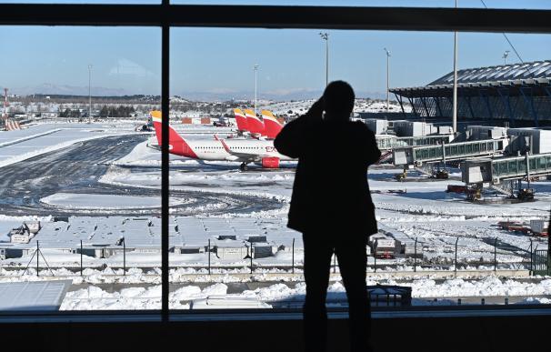 Vista de las pistas en la Terminal 4 del aeropuerto Adolfo Suárez Madrid-Barajas cubiertas parcialmente de nieve este lunes en Madrid.