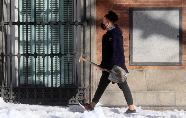 Un joven lleva una pala para despejar de nieve su calle en las inmediaciones de Atocha, en Madrid.