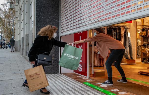 Una clienta recoge una bolsa de manos de una dependienta en un comercio del centro de Barcelona