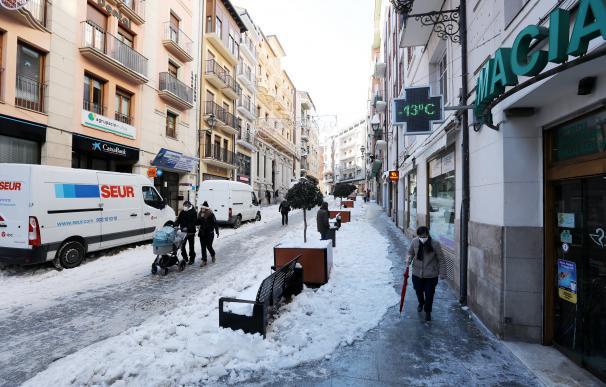 Transeúntes caminan al lado de un termómetro que marca -13 grados centígrados en el centro de la ciudad.