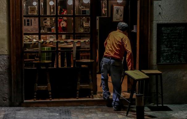 Un hombre cierra su restaurante el día en el que se adelanta el cierre de hostelería a las 22.00h, en Madrid.