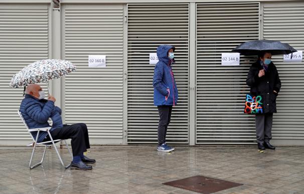 Varios votantes hacen cola en uno de los colegios electorales del Mercat de Sant Antoni de Barcelona a primera hora de este domingo.