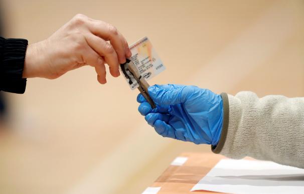 Una persona entrega su DNI a la presidenta de su mesa electoral en el Polideportivo Municipal Virrey Amat Can Ricart de Barcelona este domingo.