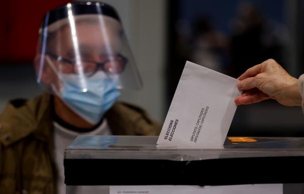 Una persona deposita su voto en el polideportivo Can Ricart del barrio del Raval de Barcelona hoy, domingo, cuando Cataluña