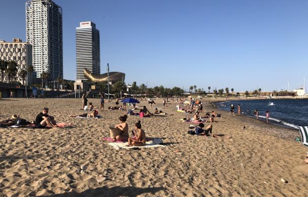 Bañistas toman el sol en la playa del Somorrostro