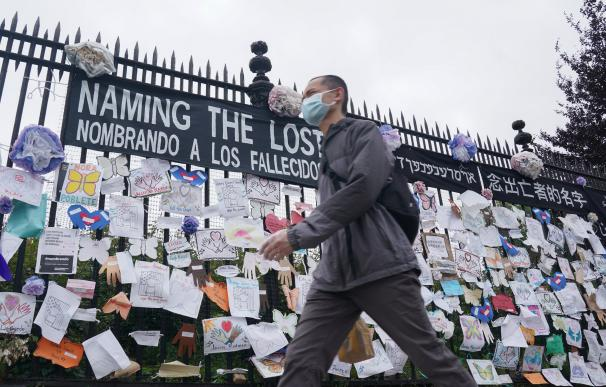 28 May 2020, US, New York: A man wearing a mask walks past a memorial for Coronavirus (Covid-19) victims hangs from a fence at the entrance to The Green-Wood Cemetery. Photo: Bryan Smith/ZUMA Wire/dpa (Foto de ARCHIVO) 28/5/2020 ONLY FOR USE IN SPAIN