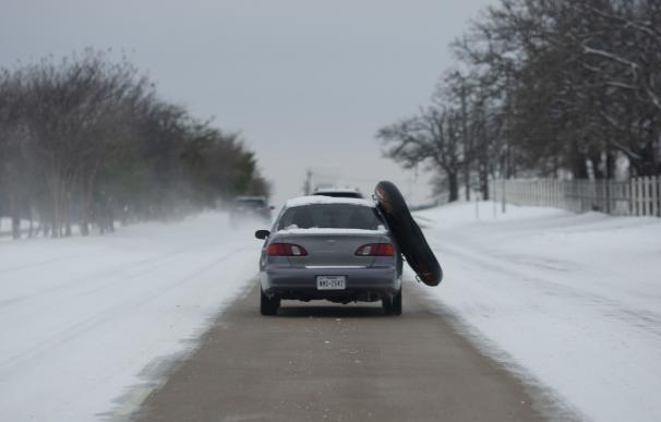 17 February 2021, US, Flower Mound: A car drives down a one-lane snow-covered road with a floating boat hanging out of their vehicle. Millions in Texas are without power after a winter storm slammed the state. Photo: Chris Rusanowsky/ZUMA Wire/dpa 17/2/2021 ONLY FOR USE IN SPAIN