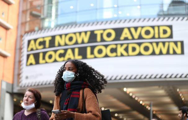20 October 2020, England, Manchester: A woman wears a face mask walks past by a sign rgarding the upcoming lockdown in Manchester. Greater Manchester will be placed under stricter coronavirus controls after last-ditch talks with the UK Prime Minister Boris Johnson aimed at securing additional financial support concluded without an agreement. Photo: Martin Rickett/PA Wire/dpa (Foto de ARCHIVO) 20/10/2020 ONLY FOR USE IN SPAIN