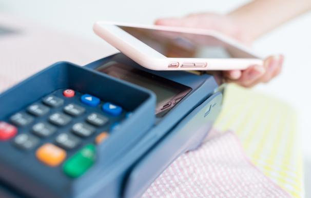 Persona pagando en un datáfono con el móvil.