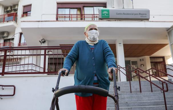 Una anciana sale de un centro residencial para mayores en Sevilla para pasear.
