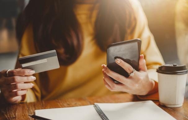 Chica joven usando tu tarjeta de crédito para pagar con el móvil.