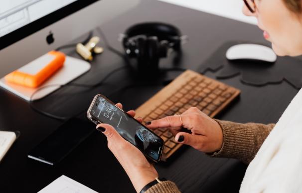 Mujer usando su teléfono móvil frente al ordenador.
