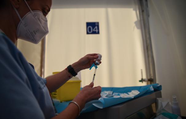 """Una profesional sanitaria sostiene una jeringuilla y un vial con la vacuna contra la Covid-19 de AstraZeneca en el Hospital de campaña de La Fe, en Valencia, Comunidad Valenciana (España), a 15 de marzo de 2021. Este lunes comienza la vacunación del personal de centros educativos --tanto docente, como de administración y servicios y otros trabajadores con contacto con el alumnado, como limpieza y monitores-- de la Comunitat Valenciana. En total, serán algo más de 116.000 personas, lo que constituirá un """"ensayo de la vacunación masiva"""" de la población. La vacuna que se va aplicar a este colectivo será de AstraZeneca, por lo que el personal que entrará en esta primera fase de vacunación a la comunidad educativa tendrá entre 18 y 55 años (el 78% del personal de la comunidad educativa potencial). 15 MARZO 2021;VALENCIA;VACUNACIÓN;CORONAVIRUS;COVID-19;ENFERMEDADES;VIRUS;CENTROS EDUCATIVOS Jorge Gil / Europa Press 15/3/2021"""