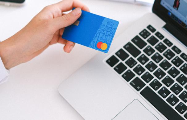 Persona pagando con su tarjeta de crédito mastercard online.